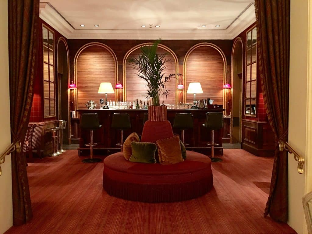 The Oleander Bar at Brenners Park-Hotel & Spa with red round couch and with dark wood bar