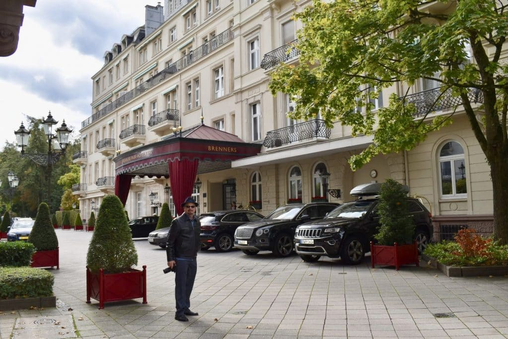 man standing outside of the front entrance of Brenners Park Hotel & Spa in Baden Baden Germany