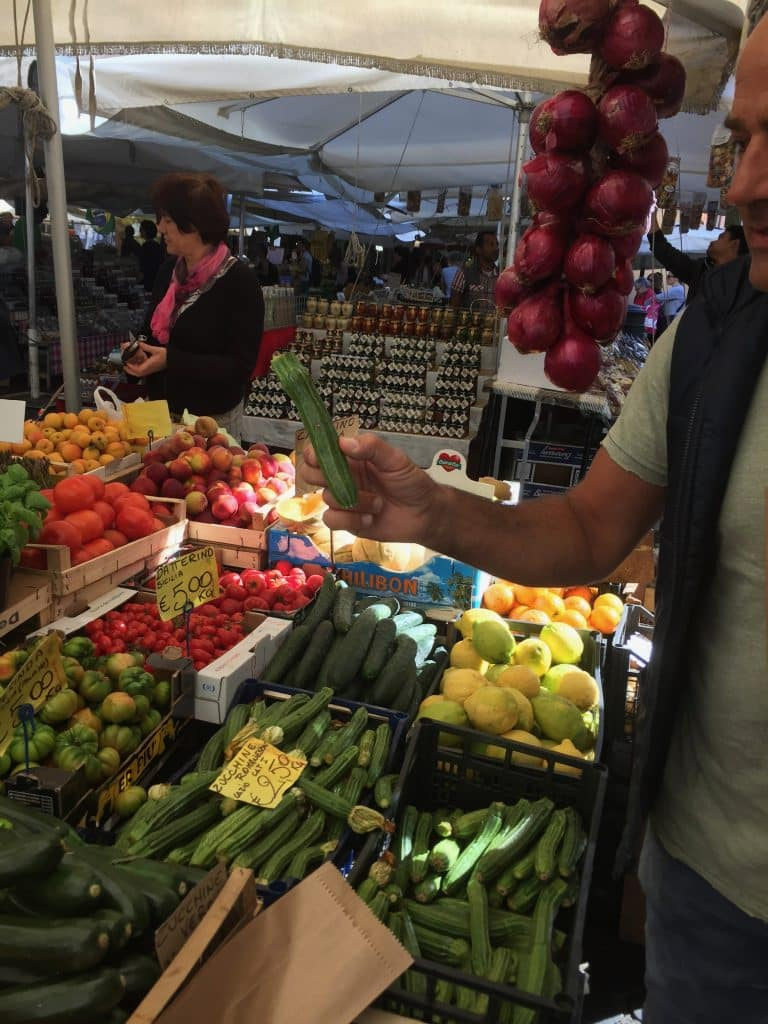 Picking out fresh vegetables and fruit in Rome market for cooking school