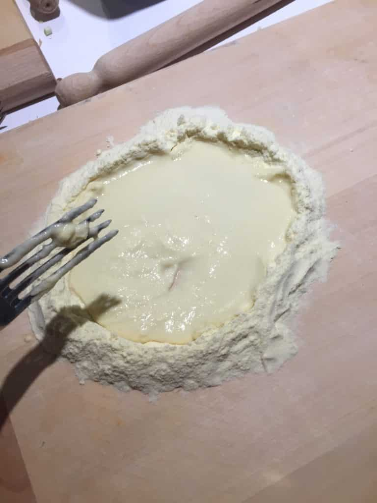 mixing flour with egg to form pasta