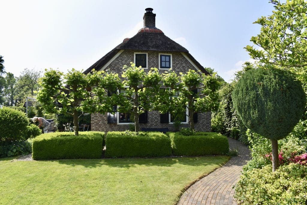 Very neat garden at a home with trees in front of home in Giethoorn Netherlands