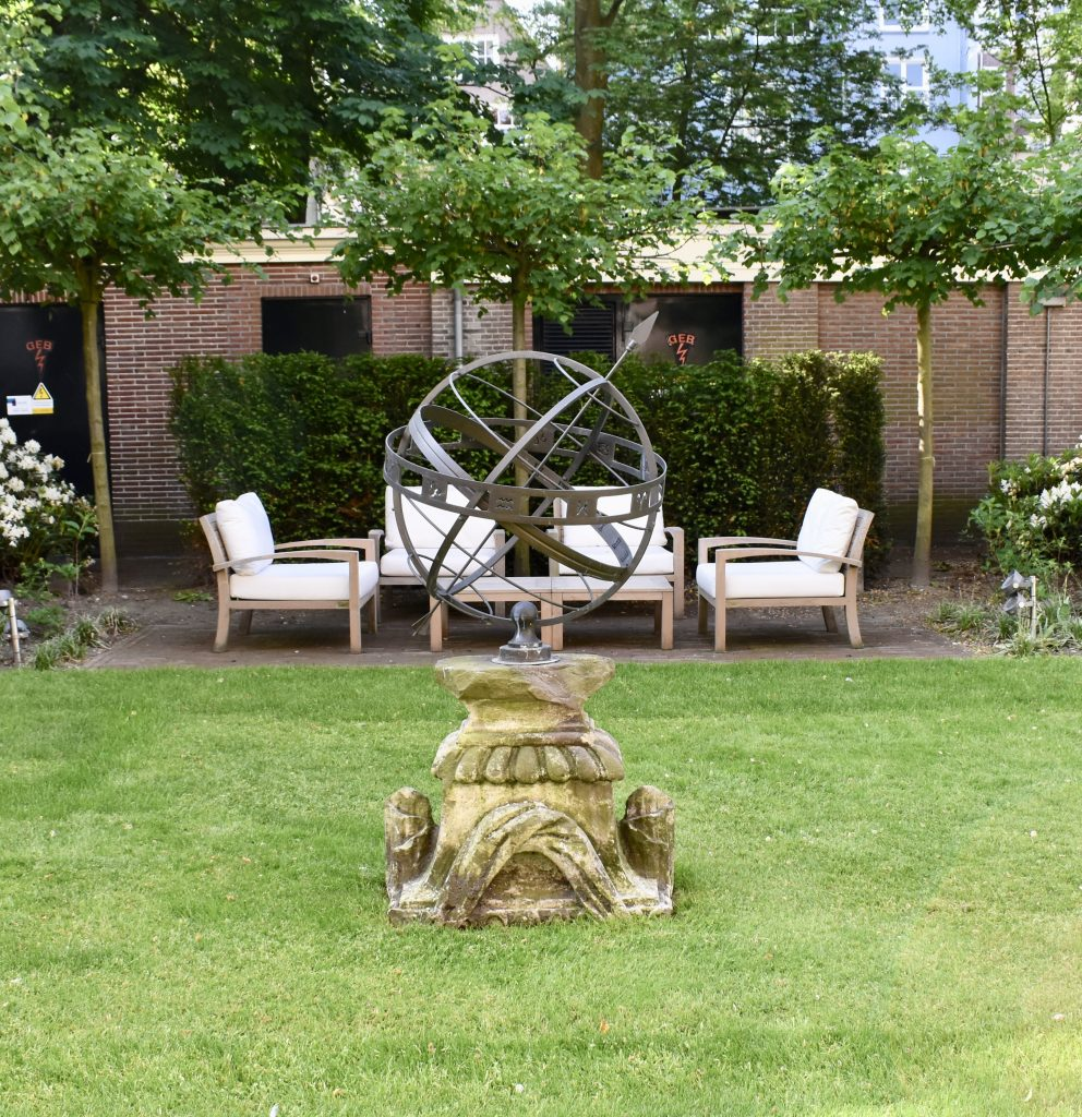 Beautiful garden with bronze globe statue at the Waldorf Astoria Amsterdam