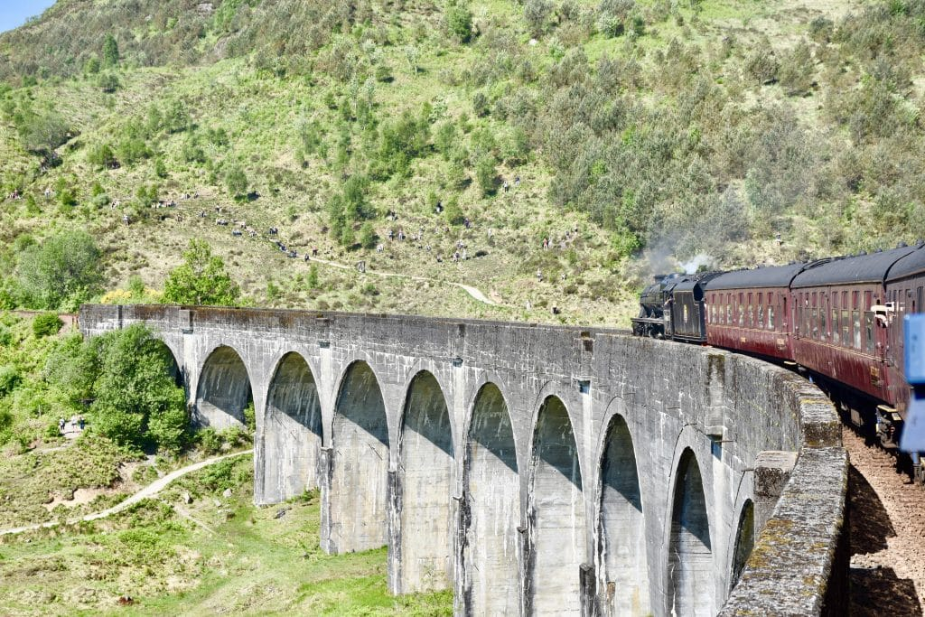 Jacobite steam train going over the Glennfinnan viaduct