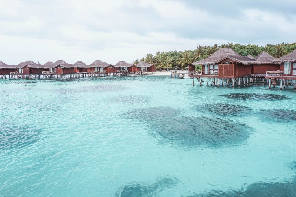 Maldives blue water with huts